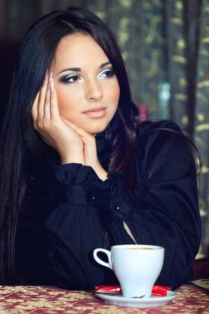 a close up portrait of a brunette drinking coffee photo