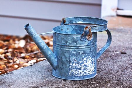 decore: Close up of a grey bucket sitting outside on a rock