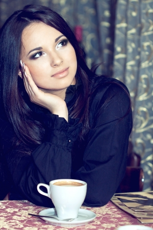 Pretty girl drinking coffee or tea and thinking photo