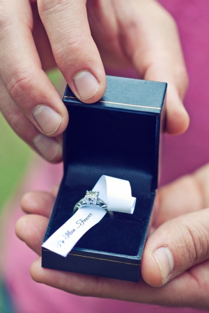 Hands holding a box with engagement ring saying be mine forever  photo