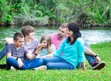 Portrait of a family sitting on a grass in the park photo