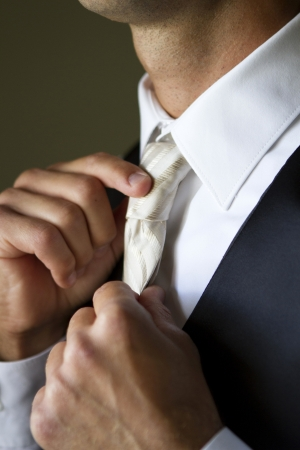 suit  cuff: Groom getting ready at the wedding indoors