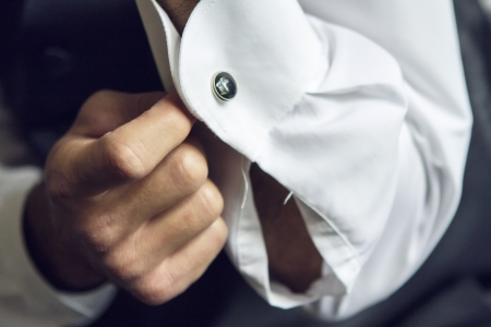 wrist cuffs: Groom getting ready at the wedding indoors
