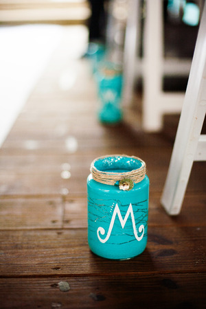 Teal jar on the wooden floor at a wedding