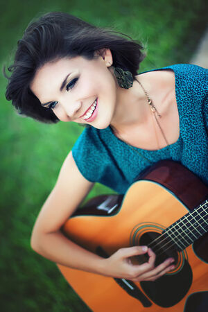 Beautiful girl playing guitar in the park photo