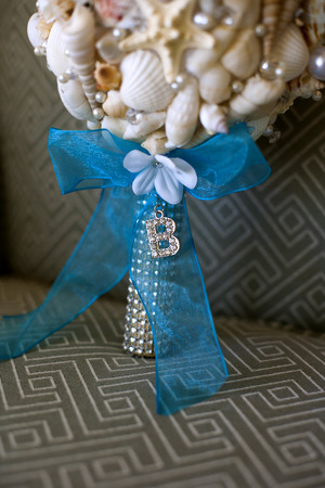 Unique bridal bouquet made of seashells on fabric chair background