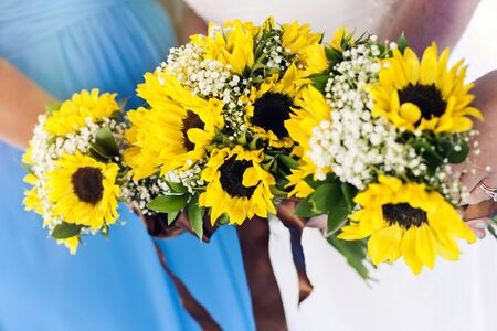 Closeup of bridesmaids holding flowers at the wedding day Standard-Bild