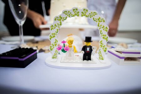 Close up of a wedding toy cake topper on a table