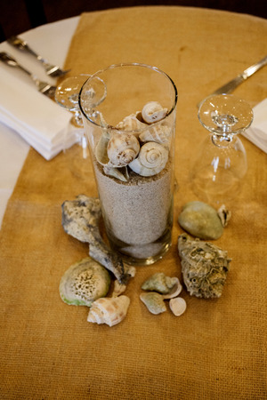 Close up of a jar with sand and shells as table decoration