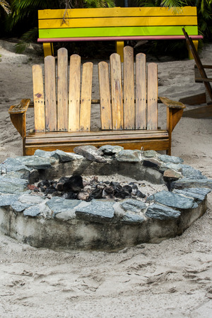 photo of a fire pit outside with a bench on the sand on the beach