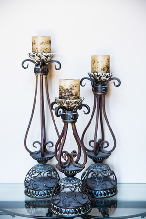 Three Candle holders  on the glass table against a white wall background