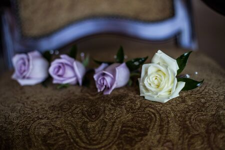 Grooms boutonnieres roses white and purple