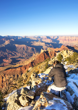 adventurer: Young man taking photograph of panoramic view of the Grand Canyon