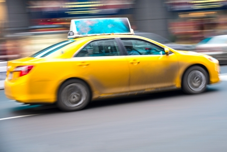 Yellow taxi accelerates in Times Square, New York