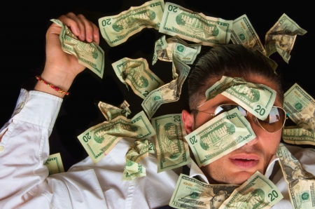 outgoings: Man covered with US dollars,drowning in debt concept