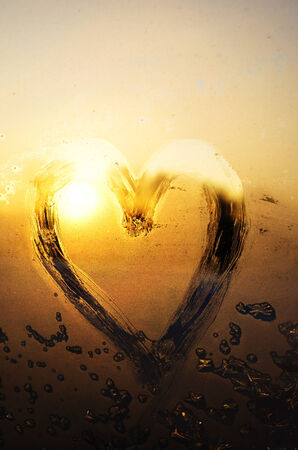 Frosty heart on window at sunset photo