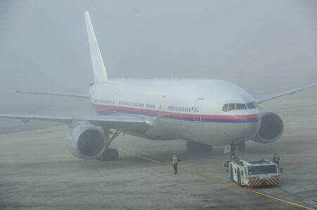 turbulence: Airplane getting ready on a foggy day Editorial