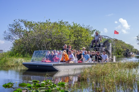 EVERGLADES, UNITED STATES - NOVEMBER 30, 2013  group of tourists riding an airboat Redakční