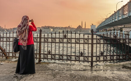 Woman taking a picture at Galata Bridge and Tower,Istanbul photo