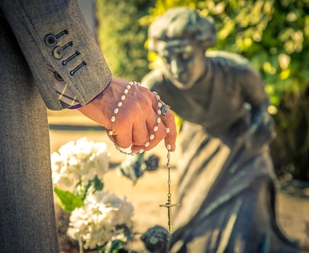 mortician: Man praying in front of a tomb with rosary in one hand Stock Photo