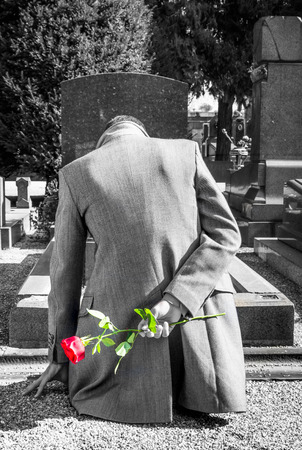 grave site: widower stands in front of his wife grave