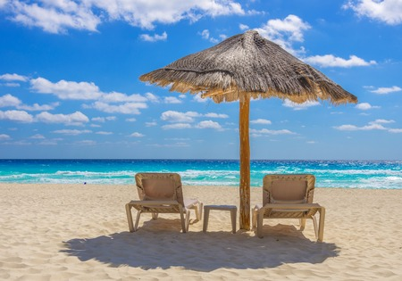 recliner: Beach chairs and umbrella on a beautiful tropical island Stock Photo