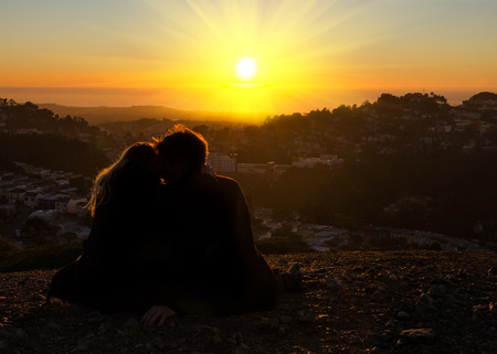 unrecognizable couple kissing in the sun photo