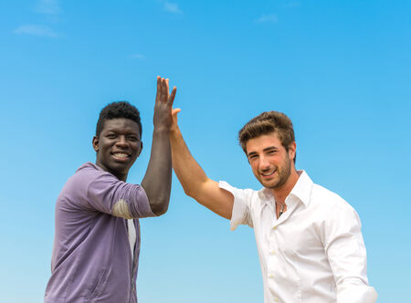 Caucasian man giving high five to a black man photo