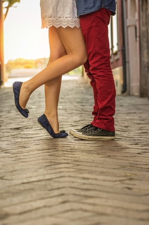 Couple kissing outdoor - close up on feet photo