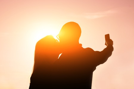 Couple kissing themself at sunset while taking a selfie with phone photo