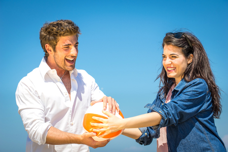 Couple having fun and playing with a beach ball photo