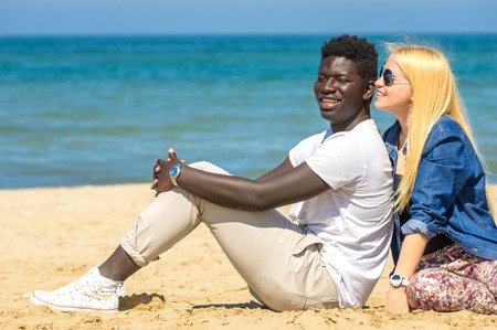 interracial couple: Young woman whispering to her boyfriend s ear