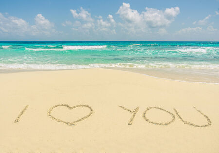 Romantic text message written on the sand   photo