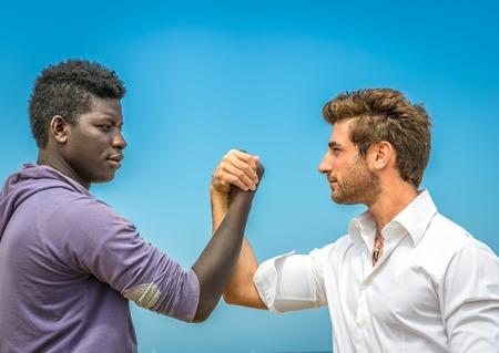 racismo: Hombre afro-americana y caucásica dar la mano - la paz, el trabajo en equipo, la colaboración, el concepto de la diversidad