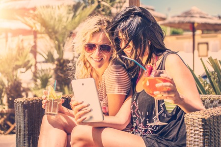 Two girls looking at phone outdoor drinking cocktails photo