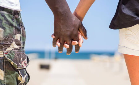 humanities: interracial couple walking on the beach Stock Photo