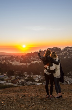 Two girls taking a selfie at the sunset photo