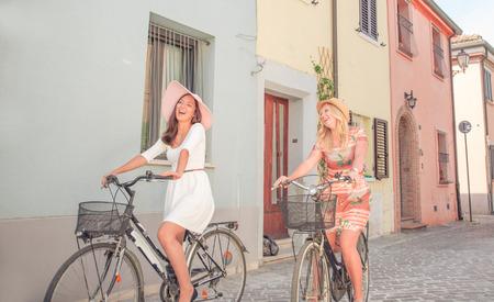 bicicleta retro: dos chicas en la bicicleta en el centro de la ciudad Foto de archivo