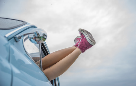woman freedom: girl with legs outside the car