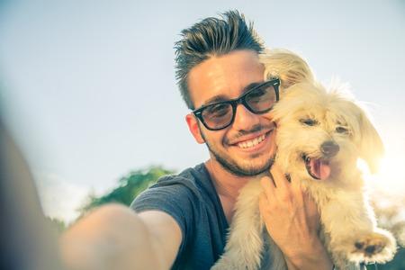 hombres jovenes: Hombre guapo joven que toma una selfie con su perro