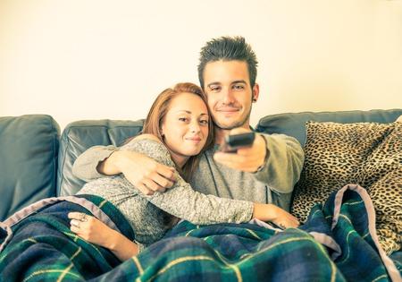 person sitting: Feliz pareja viendo la televisi�n en el sof� - familia, la recreaci�n, el ocio, concepto de la unidad