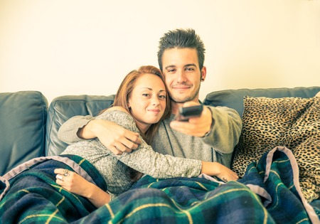 Happy couple watching television on the couch - family,recreation,leisure,togetherness concept
