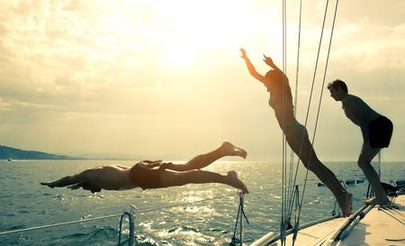 saltando: Siluetas de los ni�os de buceo desde la proa de un barco