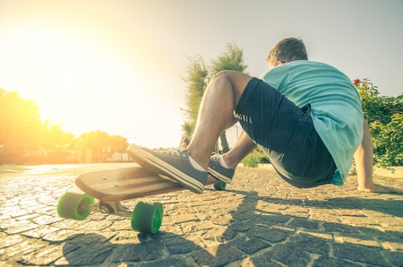 Man riding on a longboard at the sunset