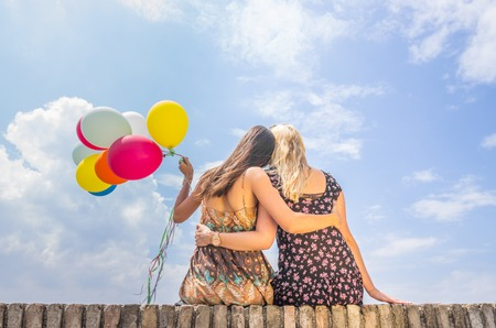 Two women hugging themselves and holding balloons - Freedom,happiness,summer concept photo