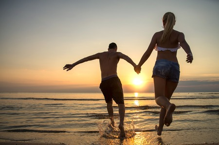 young love: Couple running into water at sunrise