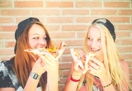 Two pretty young girls eating a slice of pizza Фото со стока