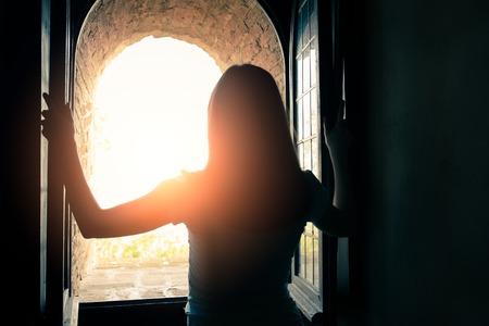 opening window: Silhoutte de la hermosa ventana de apertura de la mujer
