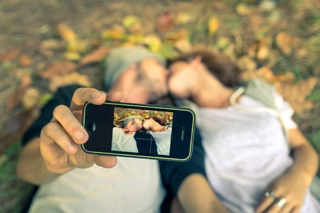 happy young couple: couple kissing while taking a selfie with smart phone Stock Photo