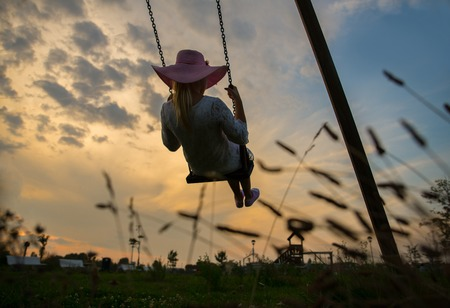 swing: Girl on swing - Young woman swinging at sunset Stock Photo
